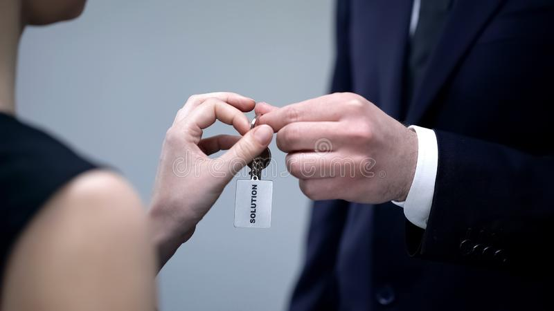 Male hand giving lady keys to Solution, help in solving business problem closeup royalty free stock photo