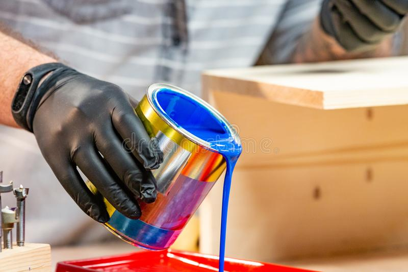 Male hand in gloves pouring paint into tray, closeup. Worker pouring blue paint into tray, closeup stock photos