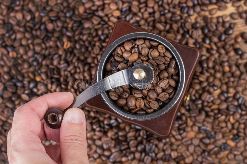 Male hand grinding coffee beans in old retro coffee mill and roasted coffee beans in background royalty free stock photo