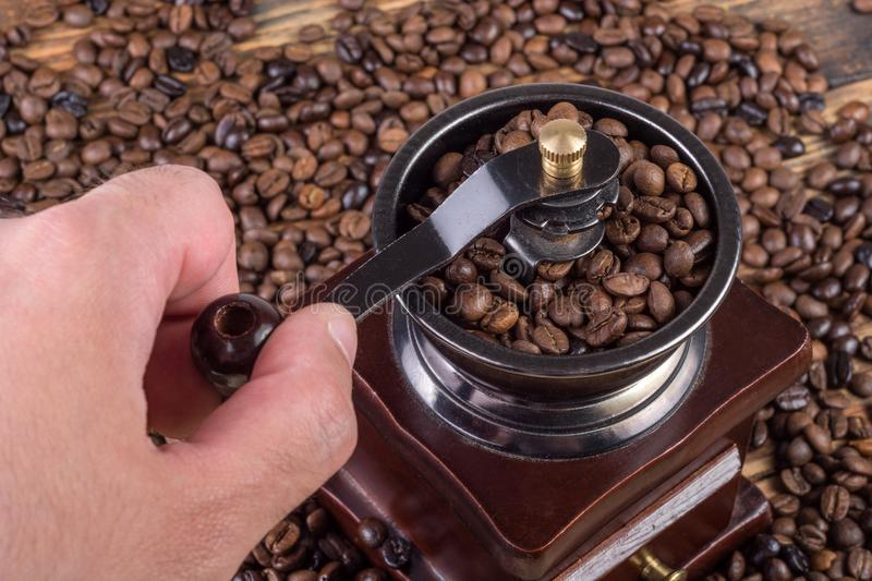 Male hand grinding coffee in old retro coffee mill and roasted coffee beans in background stock photos