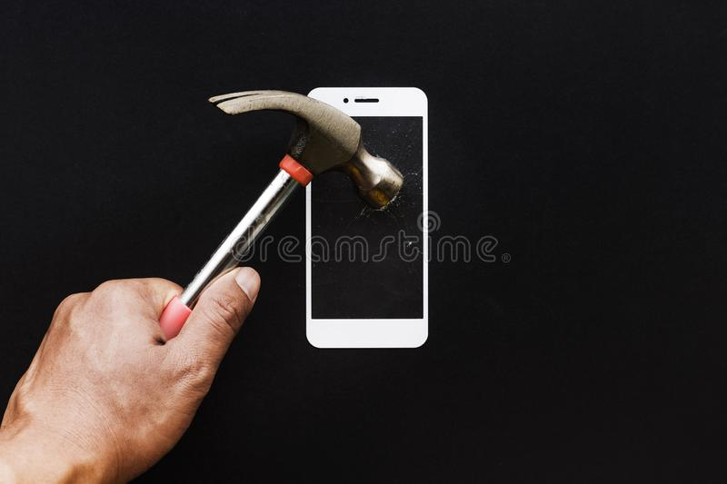 Male hand with hammer on tempered glass shield or film screen. Cover.Mobile phone protector concepts ideas stock photography