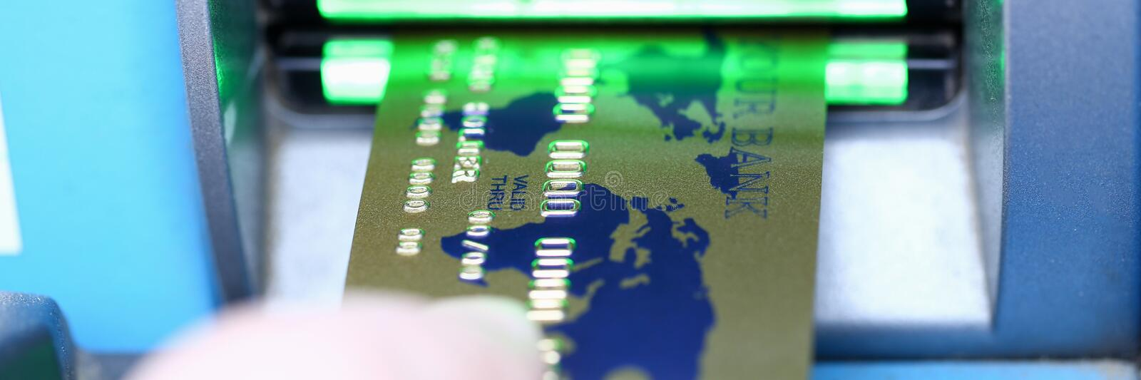 Male hand hold bank plastic card aganist atm royalty free stock photography