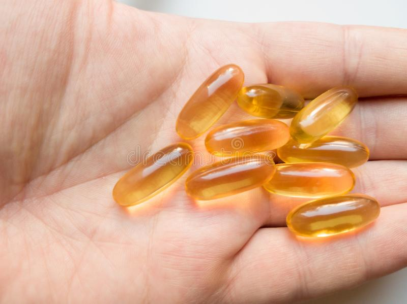 Male hand hold cod liver oil omega-3 gel capsules close-up. Hand holding capsules omega 3 or fish oil capsules isolated on white stock image