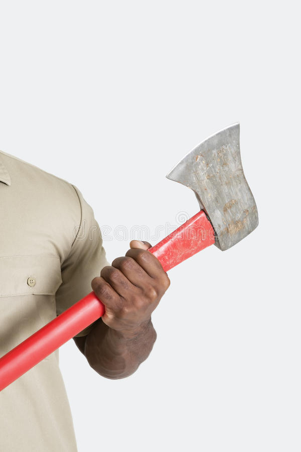 Male hand holding axe over gray background royalty free stock photo