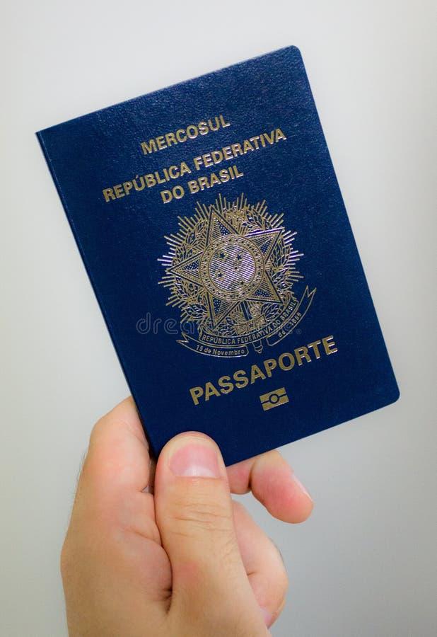 Holding a brazilian passport - previous model. Male hand holding a brazilian (previous model) passport royalty free stock image