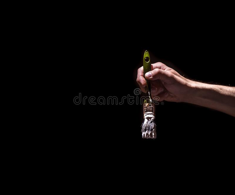 Male hand holding a brush with white paint on a black background royalty free stock photography