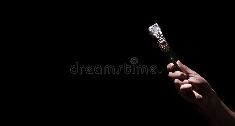 Male hand holding a brush with white paint on a black background. Man in industrial concept. royalty free stock image