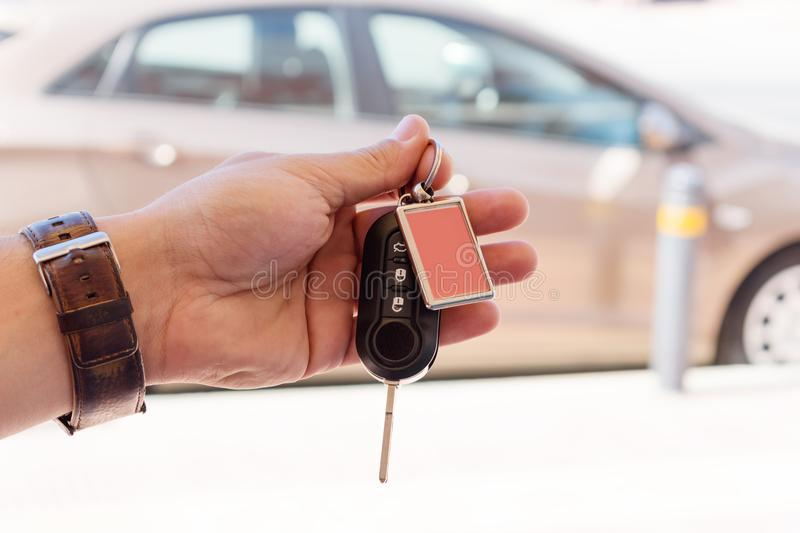 Male hand holding a car key against the brown car royalty free stock photos