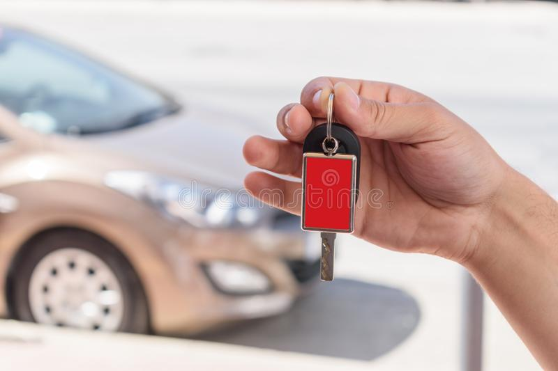 Male hand holding a car key against the brown car royalty free stock photography