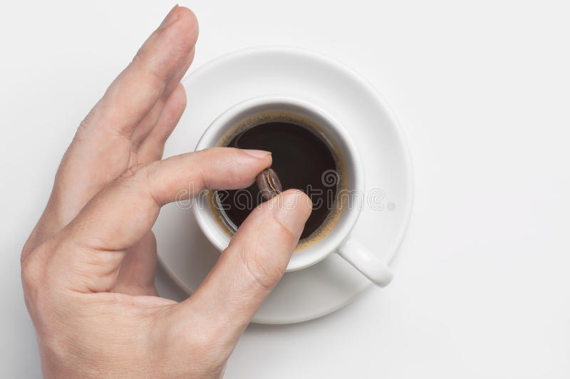 Male hand holding coffee bean over cup of black coffee against white background top view with space for text stock photo