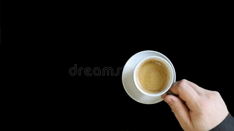 Male hand holding a coffee cup. Close up of a hand of man holding a warm mug with fresh coffee isolated on black background. stock photos