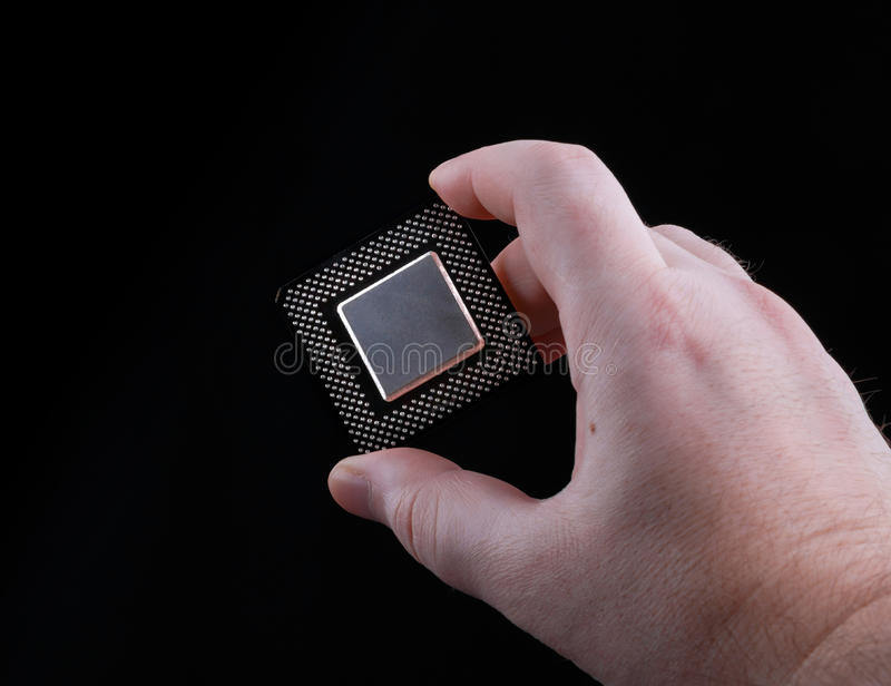 Male hand holding computer processor on black background stock images
