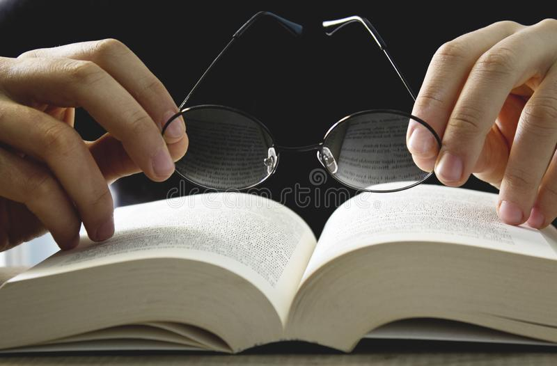 Male hand holding eyeglasses on open book. Close up stock images