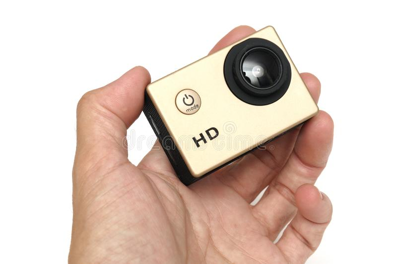 A male hand holding a gold colored small high definition HD action camera stock images
