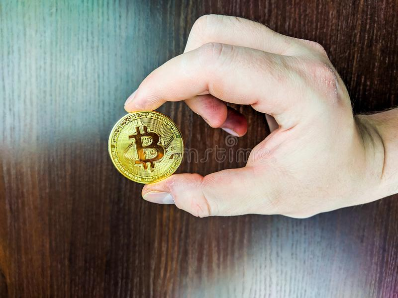 Male hand holding a golden bitcoin coin representing electronic cryptocurrency, new financial paradigm as a future currency for royalty free stock photo