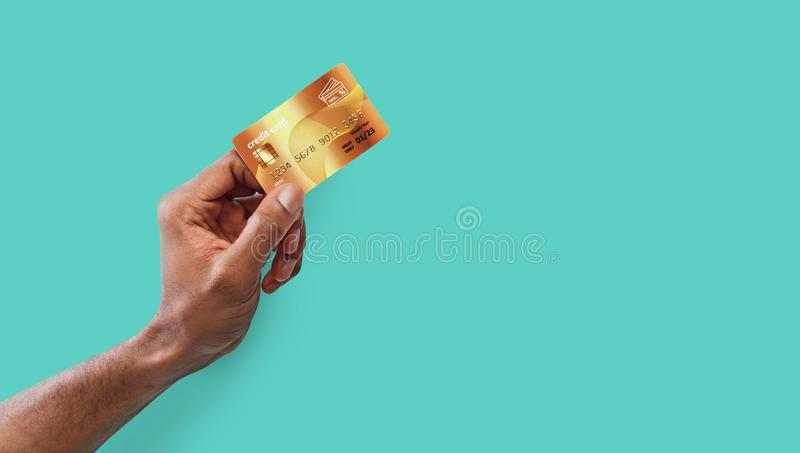 Male hand holding golden credit card on blue background stock images