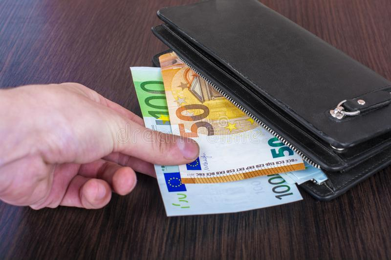 Male hand holding a leather wallet and withdrawing European currency Euro EUR stock photo
