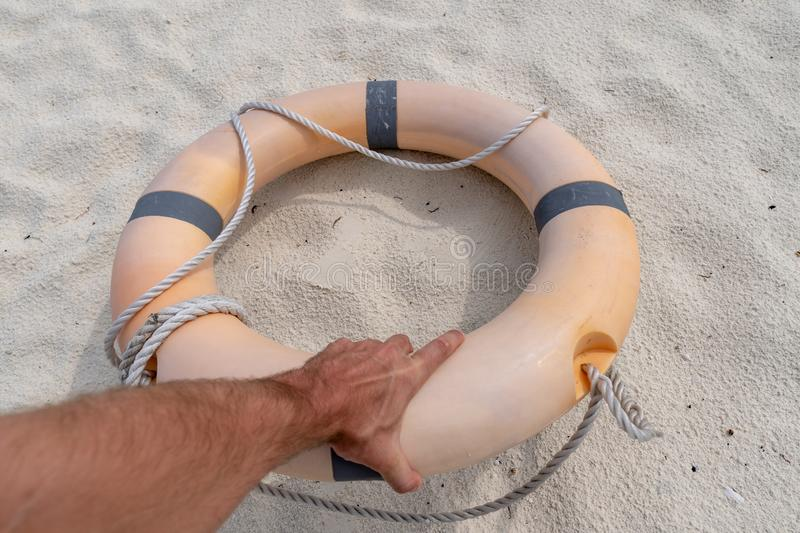 Male hand holding a life preserver. In the background sand royalty free stock photo
