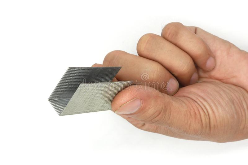 Male hand holding Metal staples for stapler isolated on white background stock photography