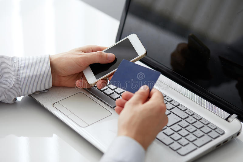 Male hand holding a mobile phone and payment. By credit card royalty free stock photo