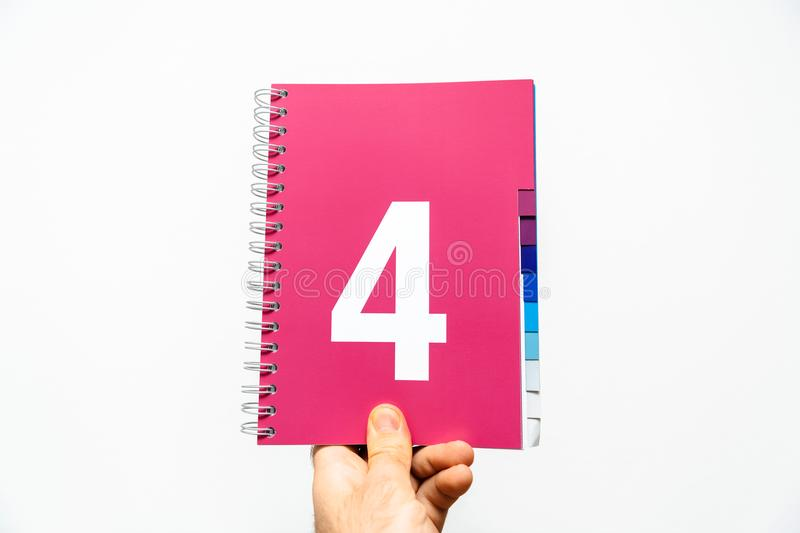 Male hand holding notebook with big number 4 on magenta stock image