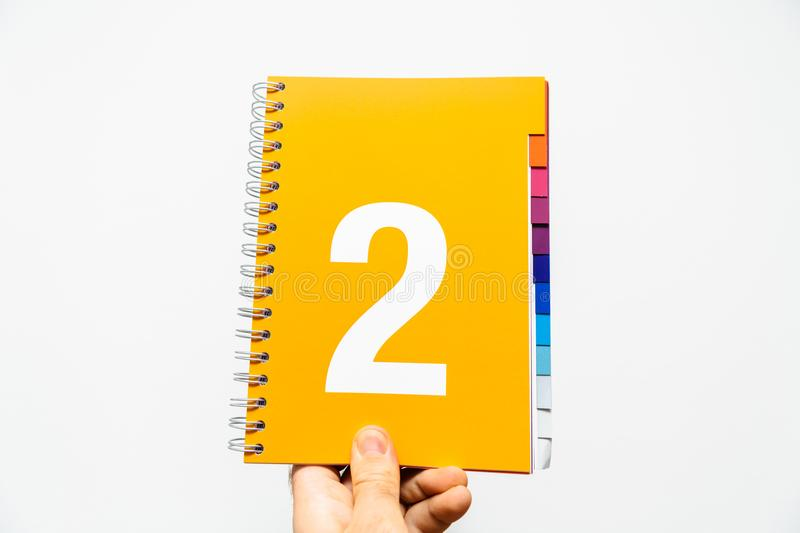 Male hand holding notebook with big number royalty free stock images