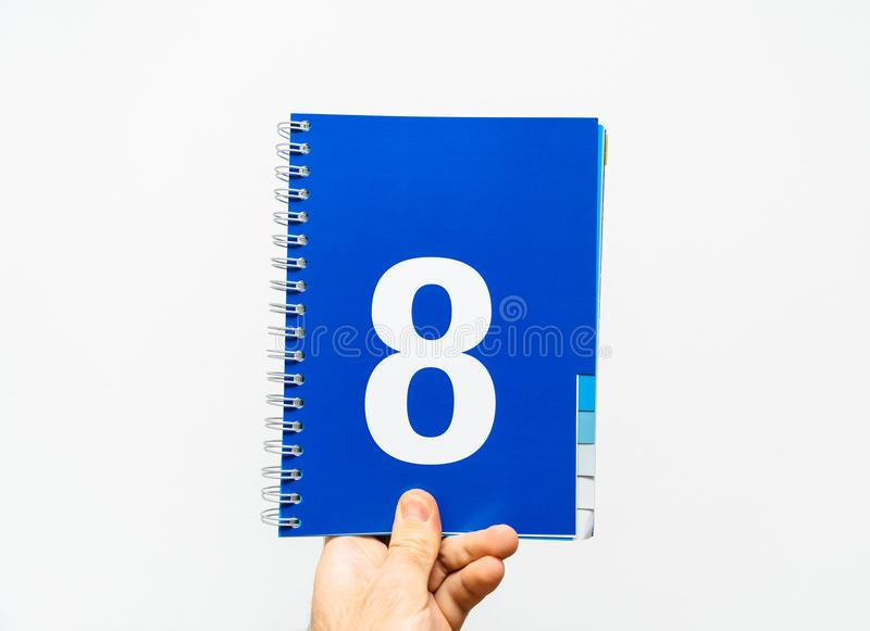 Male hand holding notebook with big number 8 on blue color, royalty free stock image