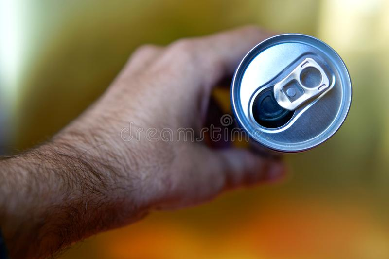 Male hand holding an open aluminum can of drink. View from above stock photo