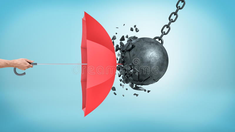 A male hand holding an open red umbrella which protects from a collision with a broken wrecking ball. stock photo