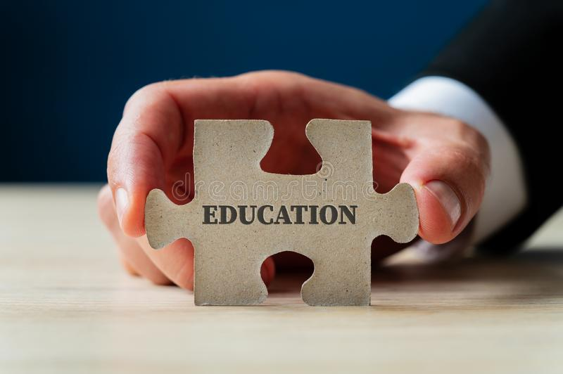 Holding a puzzle piece with education sign on it. Male hand holding a puzzle piece with education sign on it royalty free stock images