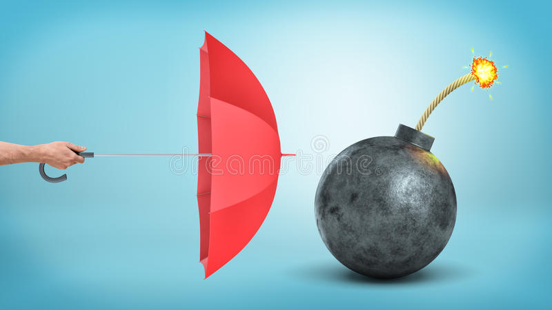A male hand holding a red open umbrella to protect from a giant round bomb with a lit fuse. royalty free stock image