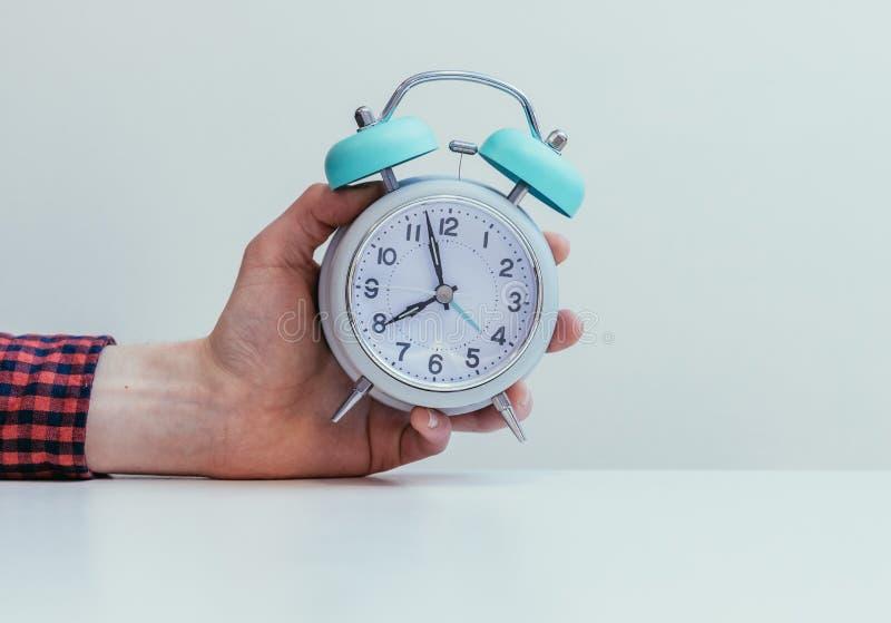 Retro styled white alarm clock in man's hand, isolated stock photo