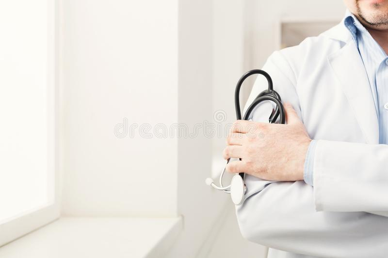 Male hand holding stethoscope in bright room closeup royalty free stock photo
