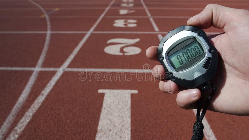 Male hand holding stopwatch with zero time, new life stage beginning fresh start stock image