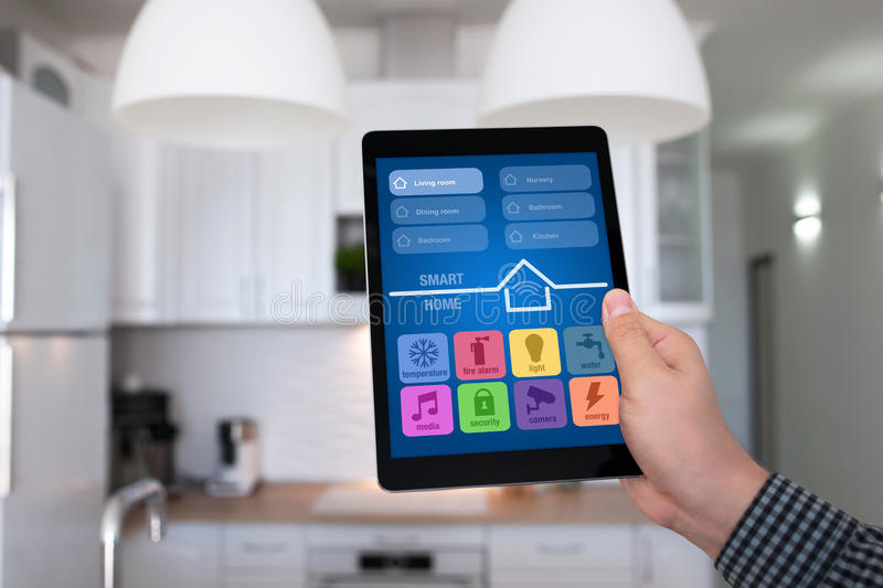 Male hand holding tablet app smart home kitchen in house. Male hand holding tablet with app smart home on background kitchen in house royalty free stock photo