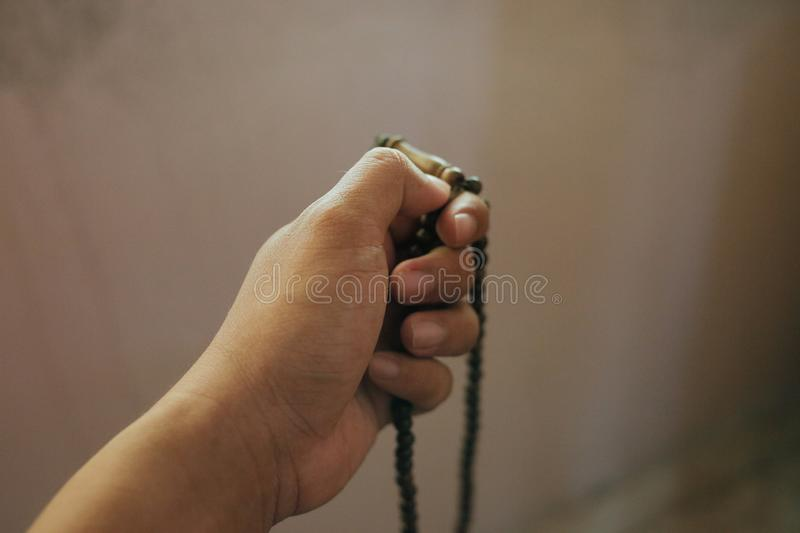 Male hand holding tasbih beads. Shot from a 45 degree angle stock images