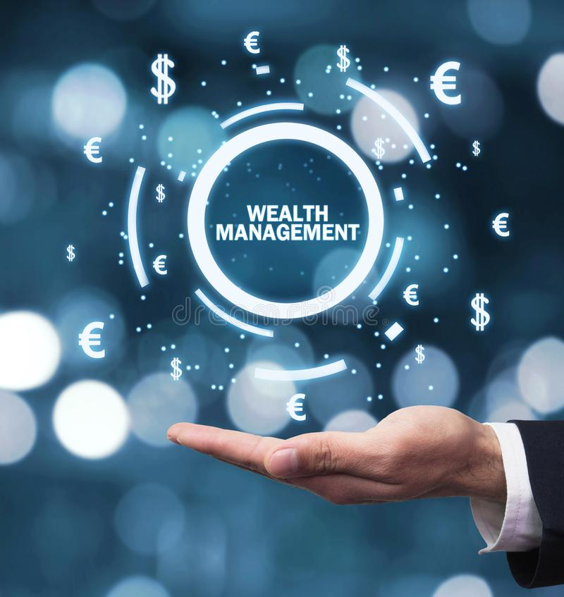 Male hand holding Wealth Management word with currency symbols royalty free stock photo