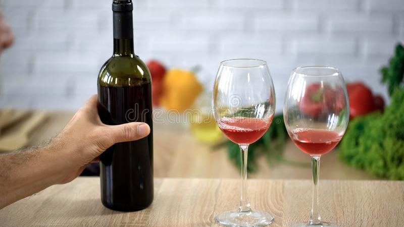 Male hand holding wine bottle, crystal glasses on table, alcohol degustation. Stock photo stock image