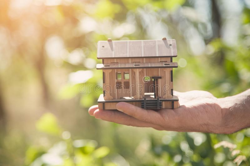 Male hand holding wooden house model in nature stock image