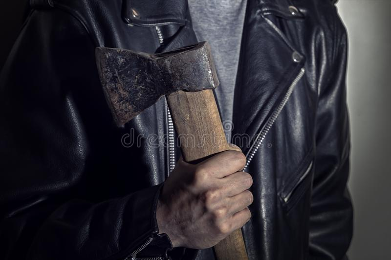 Male hand holds an ax on the background of a leather jacket. Close-up stock image