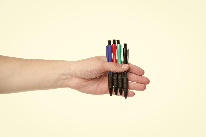 Male hand holds four pens isolated white background. Office stationery concept. He always ready to sign contract. Diversity of colorful pens. Take pen and royalty free stock photography