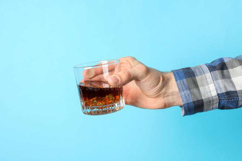 Male hand holds glass of whiskey with ice cubes on blue background stock photos