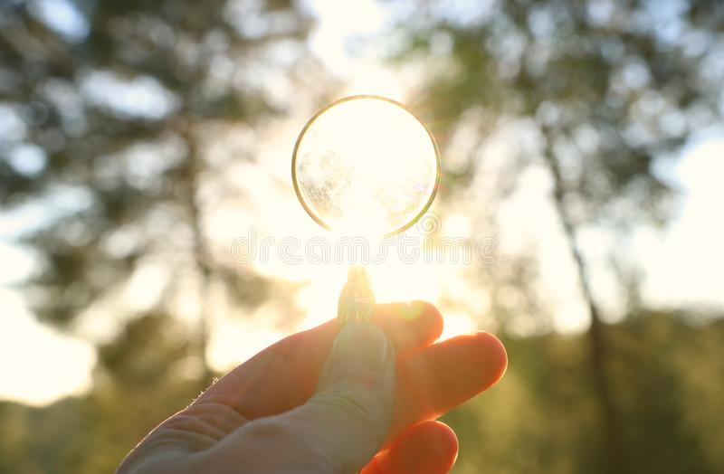 A male hand holds a magnifying glass against the setting sun outside. concept of search, creative thinking and use of solar energy. Magnifier business stock photo