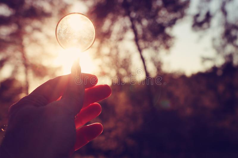A male hand holds a magnifying glass against the setting sun outside. concept of search, creative thinking and use of solar energy. Magnifier business royalty free stock images