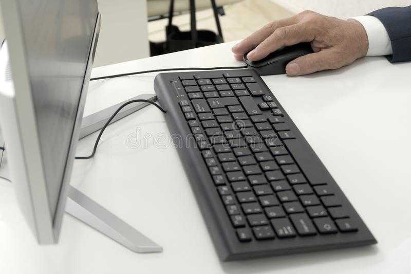 Male hand holds a mouse next to the keyboard and monitor of a personal computer on a white table. Close-up. A businessman, clerk, stock images