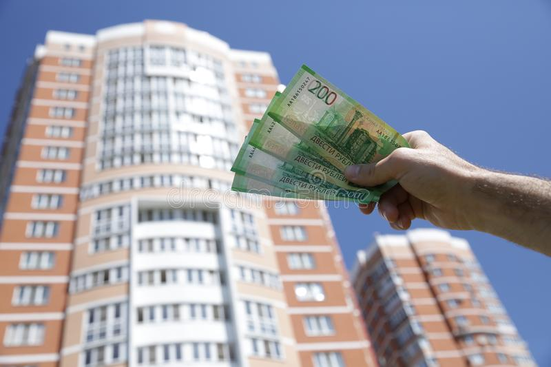 Hand holds a new Russian banknote two hundred rubles on the background of a big building and blue sky. Cash paper money stock image