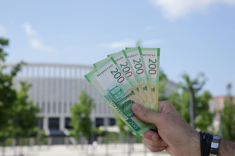 Male hand holds a new Russian banknote two hundred rubles on the background of a building and blue sky. Cash paper money stock image