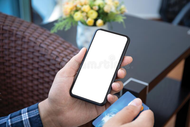 Male hand holds phone with  screen and credit card royalty free stock image