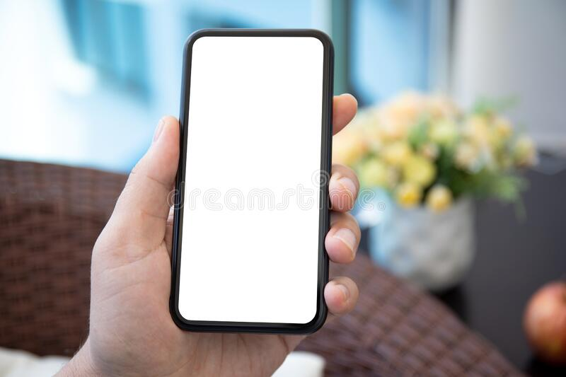 Male hand holds phone with  screen in the room stock image
