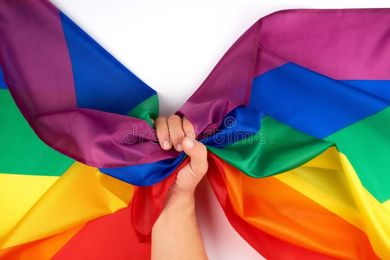 male hand holds a rainbow flag a symbol of the LGBT community stock images